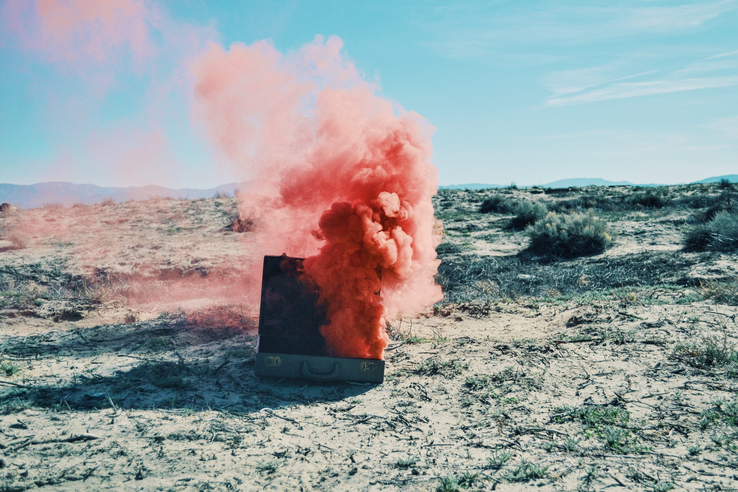 briefcase on the sand with red smoke